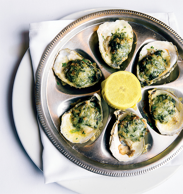 Oysters with herb and butter sauce on silver platter